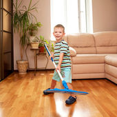Little smiling boy cleaning the room — Stock Photo