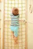 Little boy climbing on a rope net. — Stock Photo