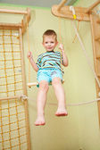 Little boy playing sports, swinging on swing — Стоковое фото