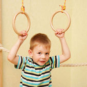 Small child exercising on gymnastic rings — Stock Photo