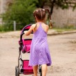Little girl walking with toy stroller. Little Mama. — Stock Photo