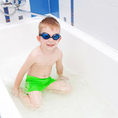 Boy washing in bath wearing glasses for swimming — Stock Photo