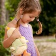 Little girl with pigtails nursing toy. — Stock Photo