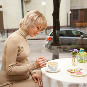 Pregnant woman having breakfast cappuccino and cookies — Stock Photo