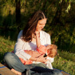 Mother taking care of baby breast feeding in the sunlight — Stock Photo
