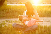 Mother breast feeding baby in the sunlight at sunset — Stock Photo