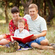 Happy father, mother and son reading book — Stock Photo