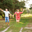 Stock Photo: Happy middle-aged couple jumping outdoors.
