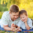 Father and son with a smartphone outdoors — Stock Photo #28932695