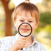Little boy smiling through magnifying glass — Stock Photo