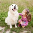 Stock Photo: Happy little girl hugging a dog