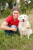 Smiling man hugging a dog — Stok fotoğraf