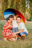 Father, mother and son with colorful umbrella. — Stock Photo