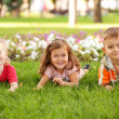 Three happy children lying on the grass — Stock Photo