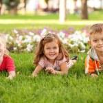 Three happy children lying on the grass — Stock Photo #30099173