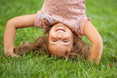 Funny happy little girl standing on her head — Stock Photo