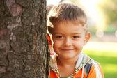 Hermoso niño sonriente junto a un árbol. — Foto de Stock