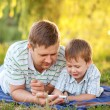Father and son playing with smartphone — Stock Photo