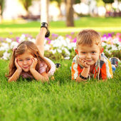 Little boy and girl among flowers. — Stock Photo