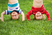 Happy kids standing upside down on grass. — Stock Photo
