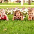 Three happy children lying on the lawn. — Стоковая фотография