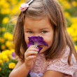 Little girl smelling flower close up.  — Stock Photo