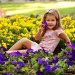 Happy beautiful little girl with flowers. — Stock Photo