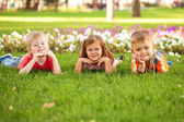 Three happy children lying on the lawn. — Stockfoto