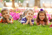 Three happy children lying on the grass — Stok fotoğraf