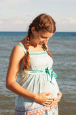 Pregnant woman hugging belly on beach — Stock Photo