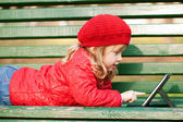 Happy little girl with tablet pc — Stock Photo