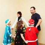 Family dancing around the Christmas tree. — Stock Photo #34709595