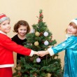Children dancing around the Christmas tree. — Stock Photo