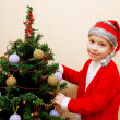 Little boy Santa decorating a Christmas tree. — Stok fotoğraf