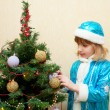 Little girl Snow Maiden decorating Christmas tree. — Stockfoto