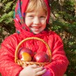 Little smiling girl with apples in a basket — Stok fotoğraf