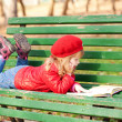 Little girl reading a book  in the park. — Stock Photo