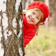 Happy little girl playing hide and seek outdoors — Stock Photo