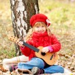 Lovely little girl playing guitar — Stock Photo