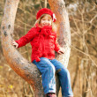 Funny little girl sitting on tree and smiling — Stock Photo