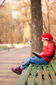 Girl reding tablet pc in the park. Computer generation — Stock Photo