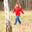 Happy smiling little girl running in forest — Stock Photo