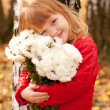 Little girl with bouquet of white flowers for the mother. — Stock Photo