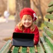 Happy smiling little girl using tablet — Stock Photo