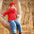 Funny little girl sitting in a tree — Stock Photo #35240783