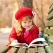 Happy smiling little girl reading interesting book — Stock Photo