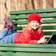 Smiling happy little girl using tablet outdoors. — Stock Photo