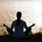Silhouette of woman in meditative pose — Stock Photo