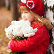 Smiling little girl with bouquet of white flowers — Stock Photo
