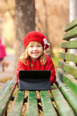 Happy smiling little girl with tablet pc — ストック写真